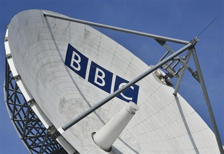 A satellite transmission dish is seen behind housing near BBC Television Centre at White City in London