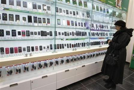 A customer looks at a display of handsets for sale inside a MegaFon shop in St. Petersburg