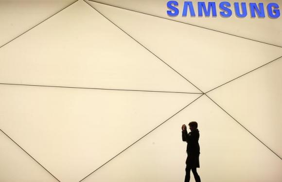 A woman takes a picture outside the Samsung stand at the Mobile World Congress in Barcelona
