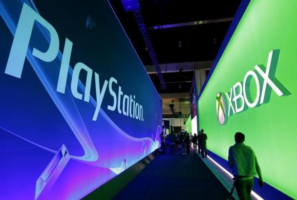 People walk past the Playstation and Xbox booths at the 2014 Electronic Entertainment Expo, known as E3, in Los Angeles