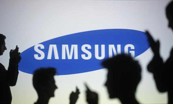 File photo of people posing with mobile devices in front of projection of Samsung logo in Zenica