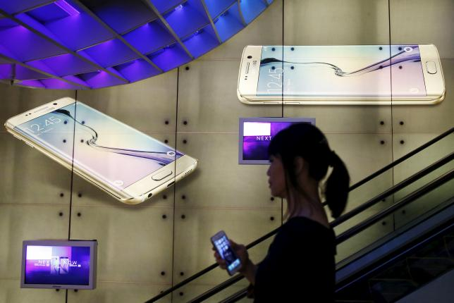 A woman holding an Apple iPhone passes a Samsung Galaxy S6 advertisement at a mall in Singapore