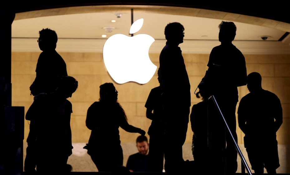 Customers stand beneath an Apple logo at the Apple store in Grand Central station in New York City