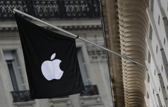 An Apple logo is seen on a flag on the facade of the Apple Store in Paris