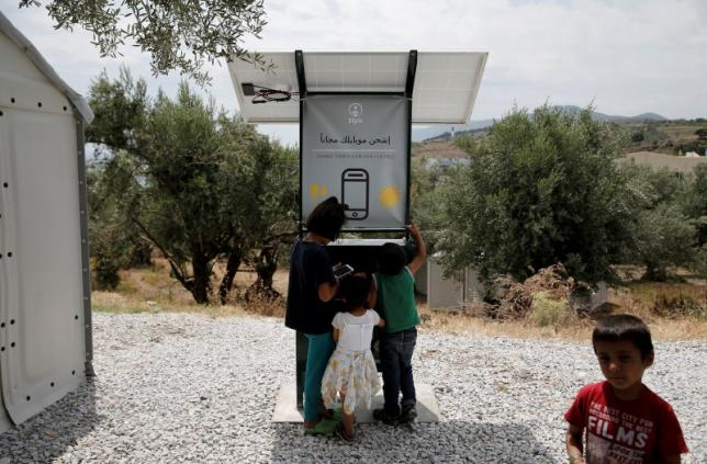Children stand around a solar powered charging station for mobile devices designed by a group of university students, at the municipality-run camp of Kara Tepe on the island of Lesbos