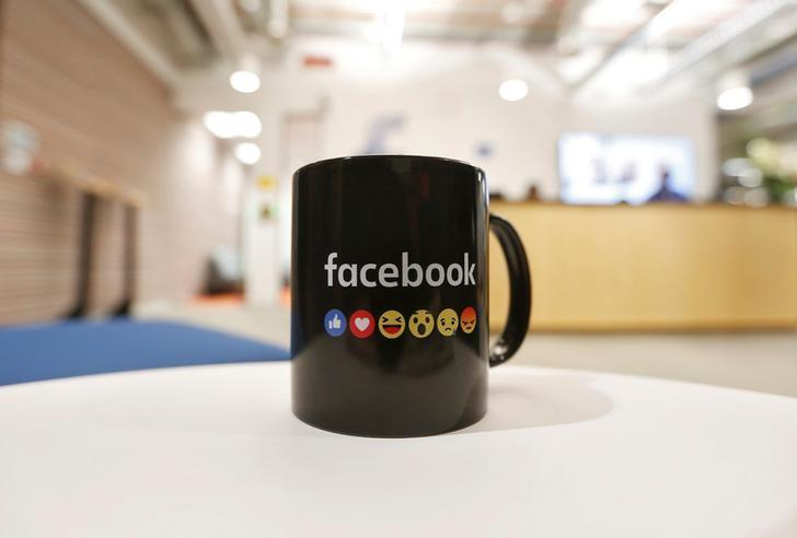 The Facebook logo and emoticons are seen on a coffee mug at the reception of its new office in Mumbai, India May 27, 2016. REUTERS/Shailesh Andrade