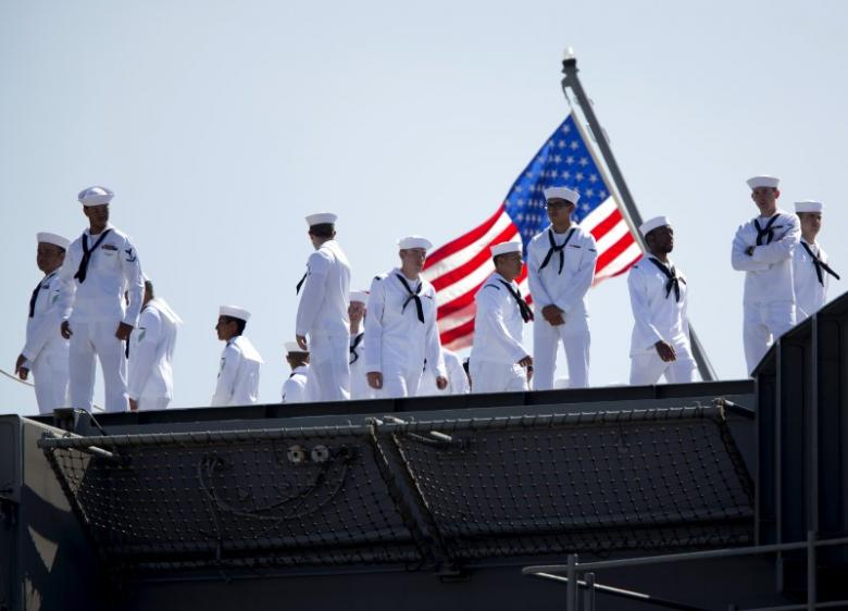 Sailors man rails as USS Ronald Reagan departs for Yokosuka, Japan from Naval Station North Island in San Diego