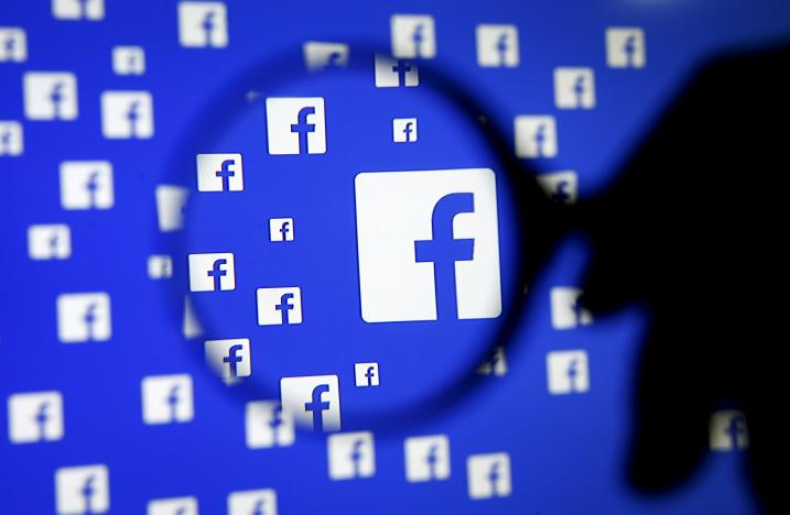 A man poses with a magnifier in front of a Facebook logo on display in this illustration taken in Sarajevo, Bosnia and Herzegovina, December 16, 2015. REUTERS/Dado Ruvic/File Photo