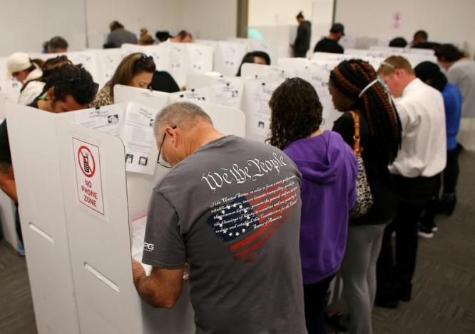 A voter wears a shirt with words from the United States Constitution while casting his ballot early as long lines of voters vote at the San Diego County Elections Office in San Diego, California
