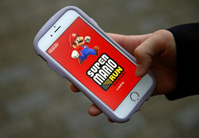 "Takuya Nishya shows Nintendo's ""Super Mario Run"" game on his smartphone by the request of a photographer in Tokyo"