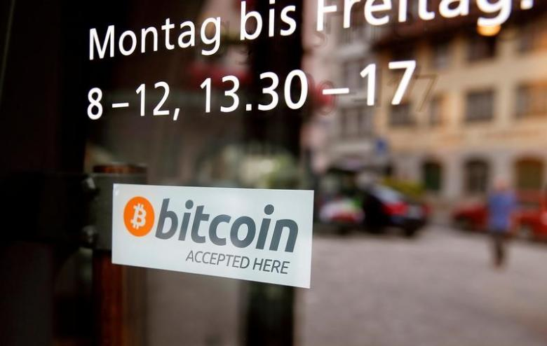 "A sticker that reads ""Bitcoin accepted here"" is displayed at the entrance of the Stadthaus town hall in Zug, Switzerland, August 30, 2016. REUTERS/Arnd Wiegmann"